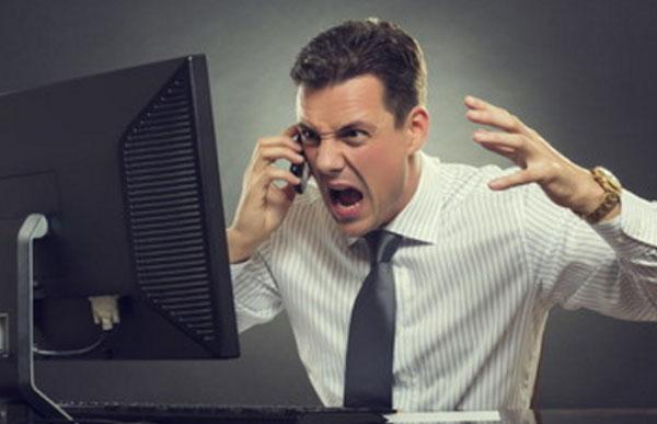мужчина сидит за компьютером, в руках у него телефон. Он эмоционально общается