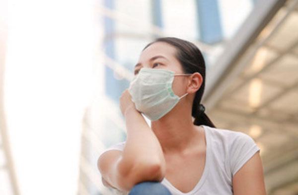 Женщина сидит на улице с маской на лице