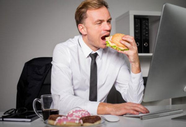 Мужчина сидит за ноутбуком и ест бургер. На столе лежат пончики