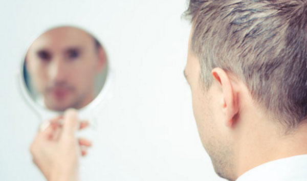 Парень смотрит на себя в зеркало