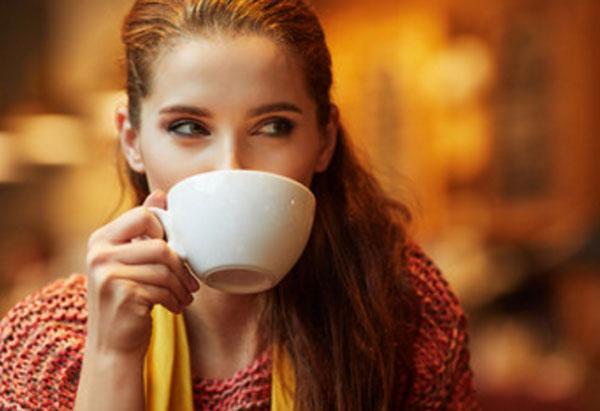 Девушка пьет чай в кафе и строит кому-то глазки