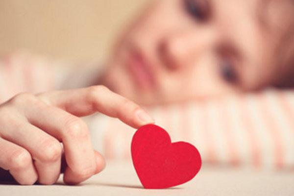 На переднем плане рука девушки, удерживающая картонное сердечко. На заднем плане ее лицо