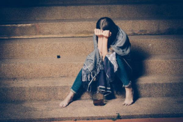 Девушка сидит на ступеньках. Она прячет свое лицо