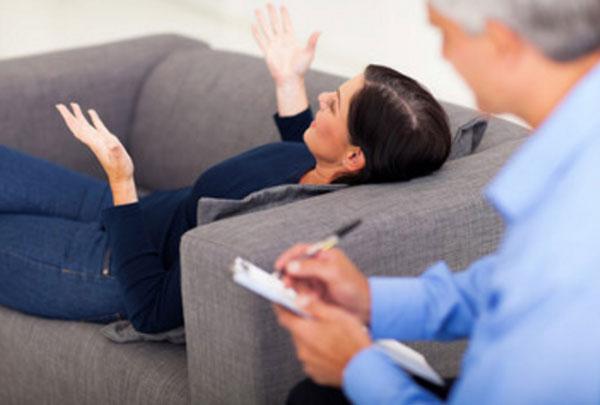 Женщина лежит на диване и общается с психологом