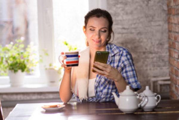 Девушка дома сидит за столом в простой одежде, без макияжа и переписывается по телефону