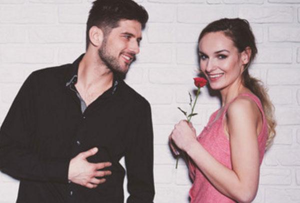 Парень смотрит на девушку влюбленными глазами. Она улыбается и держит в руке розу