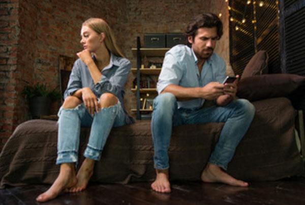Серьезные мужчина с женщиной сидят на кровати