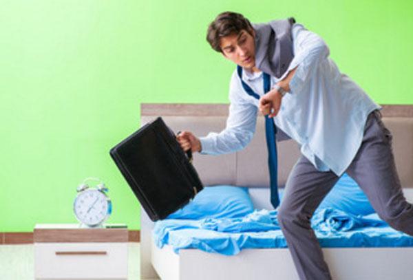 Мужчина впопыхах покидает свою комнату с чемоданом в руке