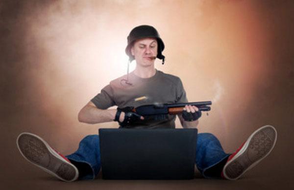 Мужчина сидит в шлеме и с оружием в руке. Перед ним на полу ноутбук