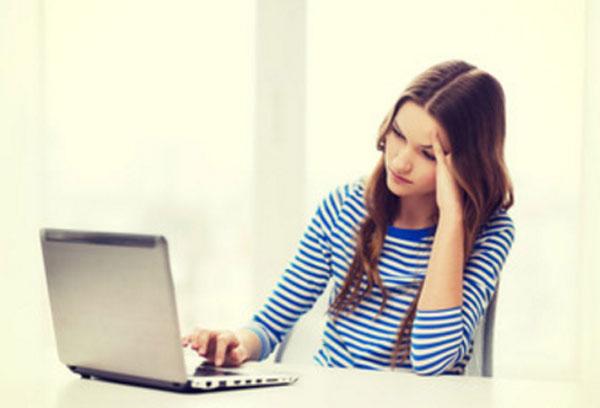 Грустная девушка сидит перед ноутбуком, что-то на нем смотрит