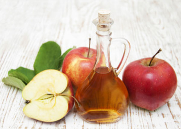 На столе стоит яблочный уксус. Рядом с ним лежат яблоки