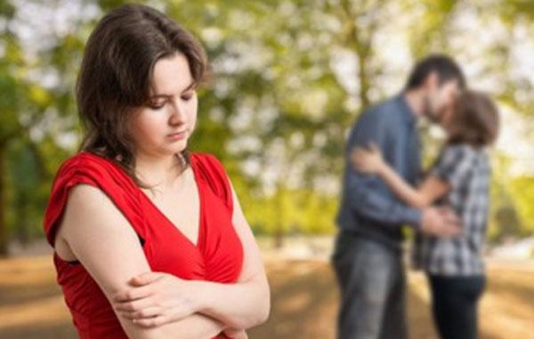 Расстроенная девушка, на заднем плане ее парень целует другую