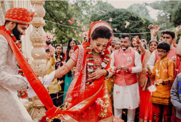 Индийская свадебная церемония. невеста в красном наряде, у жениха красный головной убор