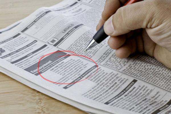 Человек обвел красной ручкой объявление с вакансией в газете