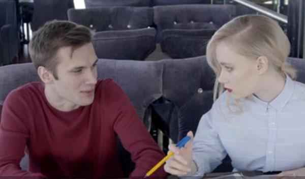 Мужчина и женщина сидят за столом. Женщина держит ручку