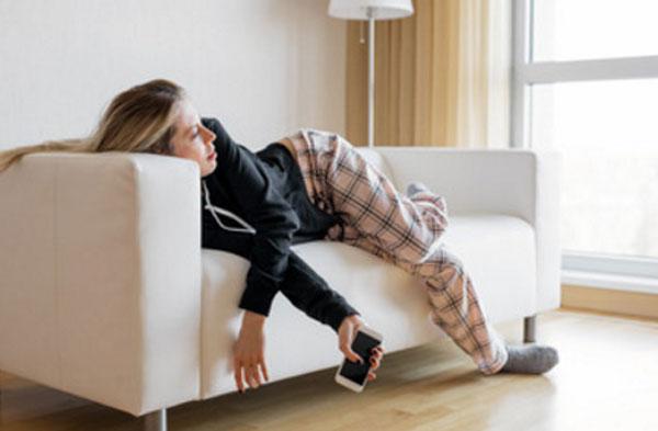 Обессиленная женщина лежит на диване