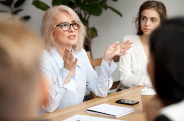 Женщина в очках объясняет что-то сотрудникам, сидящим за столом