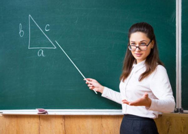 Строгая учительница в очках стоит возле доски с указкой в руке