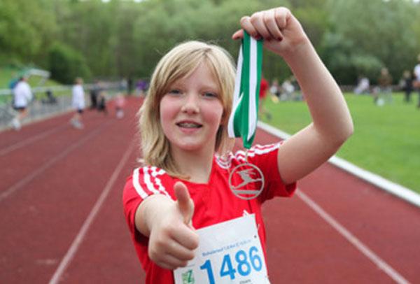 Ребенок стоит с медалью в руках, показывает &quot,класс&quot,