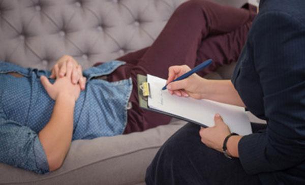 Человек лежит на диване и общается с психотерапевтом