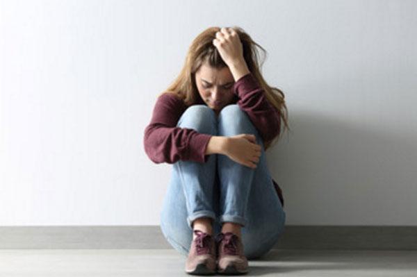 Женщина сидит на полу. Она в депрессии