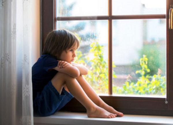 Ребенок сидит на окне