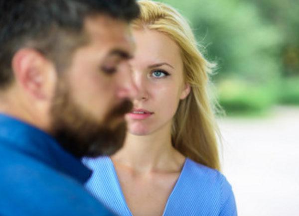 Парень стоит боком, за ним девушка