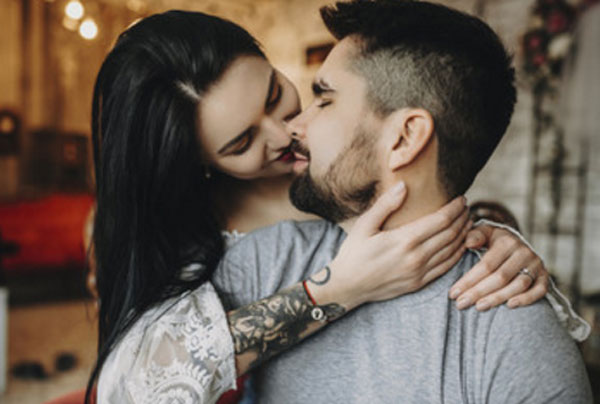 Женщина обняла сзади мужчину. Пытается его поцеловать