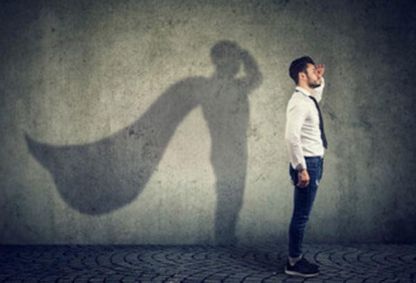 Мужчина стоит, держа руку у виска. Сзади него тень на стене, у которой за спиной расправляется плащ супергероя