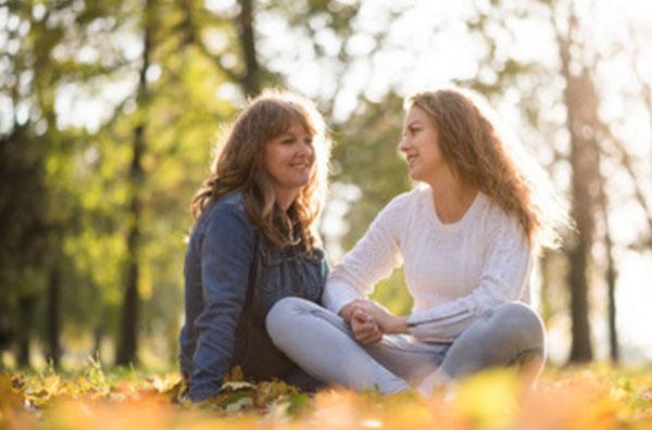 Мама общается со взрослой дочерью, сидя на осенней листве