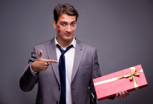 Мужчина со следами от поцелуев на лице держит подарок