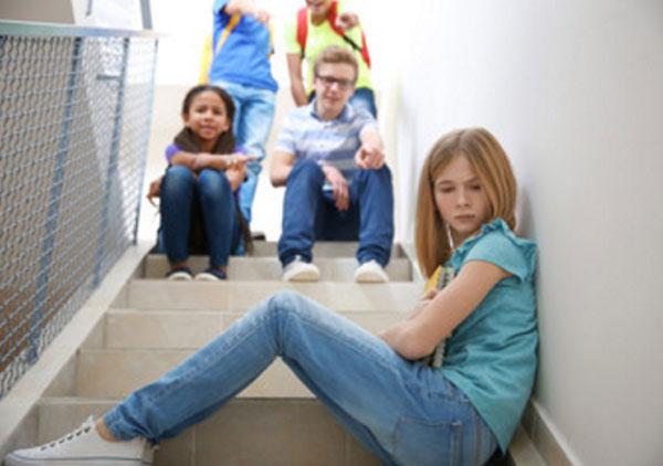Девочка сидит поперек ступенек. Выше нее находятся ребята