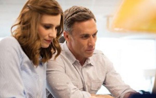 Грустная женщина сидит рядом с серьезным коллегой