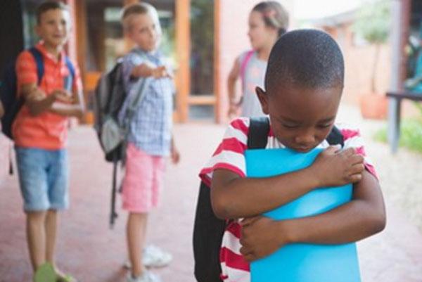 Дети насмехаются над мальчиком негроидной расы, который очень расстроен