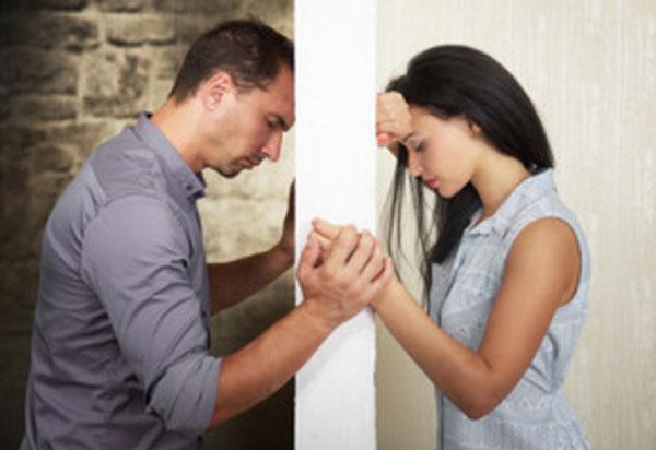 Мужчина и женщина стоят напротив друг друга, их разделяет стена