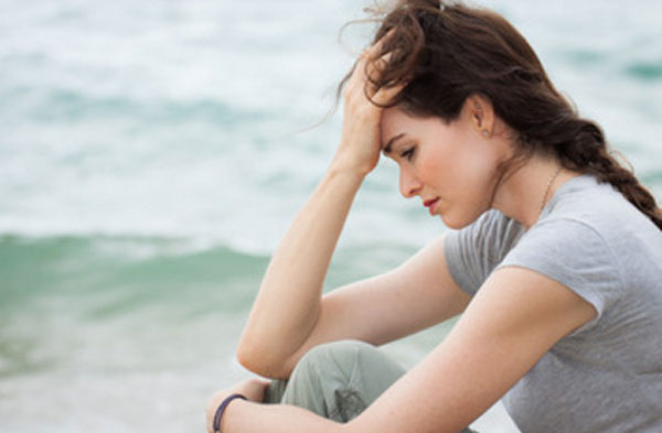 Расстроенная девушка сидит у моря