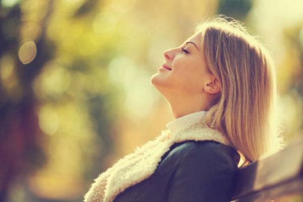 Счастливая женщина сидит в парке на скамейке, греется под лучами солнца