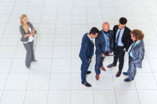 Расстроенная женщина стоит в сторонке от компании мужчин, которые что-то активно обсуждают. Все в костюмах.