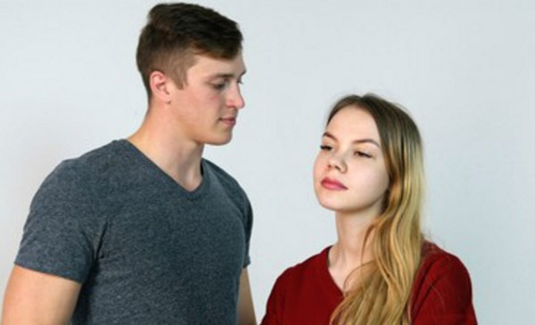 Серьезные парень с девушкой. Он смотрит на нее. А она глядит вдаль