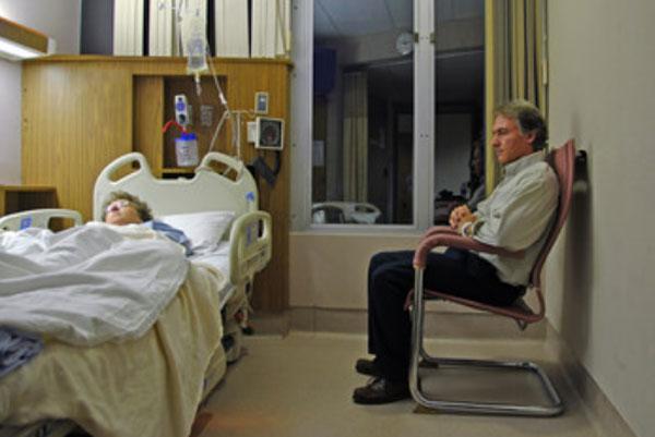 Мужчина сидит возле кровати больной женщины