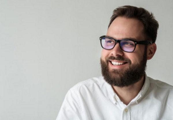 Улыбающийся мужчина с бородкой и в очках