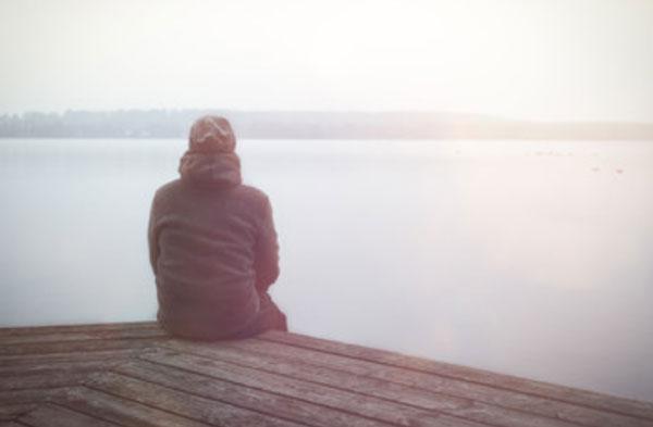 Мужчина сидит на пирсе в гордом одиночестве