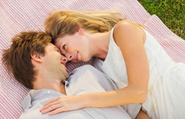 Парень с девушкой лежат на покрывале, смотрят друг на друге влюбленными глазами