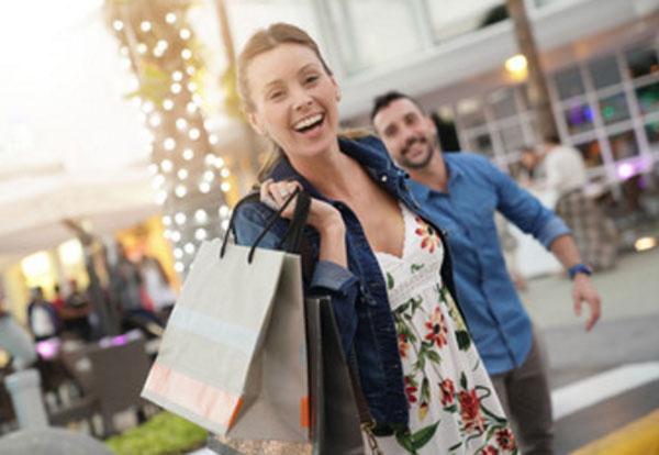 Девушка с покупками, сзади волочится парень