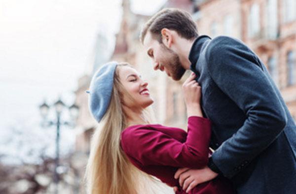 Парень хочет поцеловать девушку. Она слегка отклоняется от него, при этом улыбается