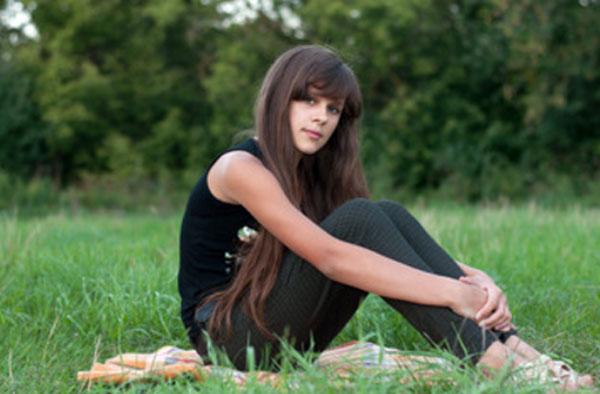 Девочка - подросток сидит на траве