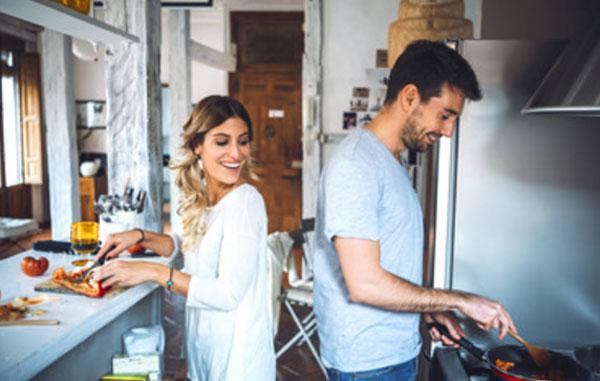 Муж с женой готовят ужин. Она нарезает, а он что-то жарит на сковороде