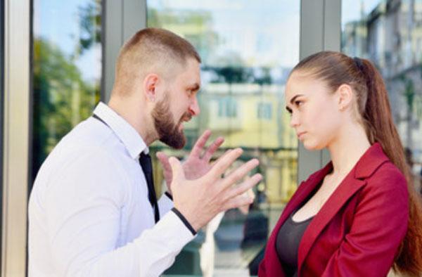 Злой мужчина что-то высказывает девушке