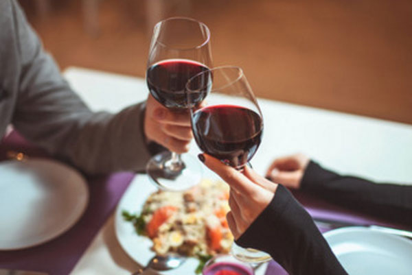 Пара сидит за столом, супруги подняли бокалы с вином