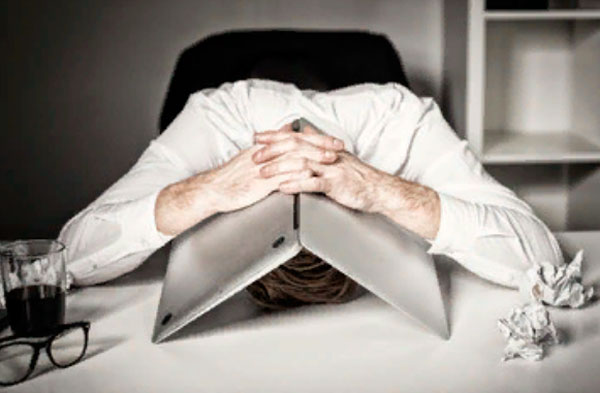 Мужчина положил голову на стол и накрыл лицо ноутом